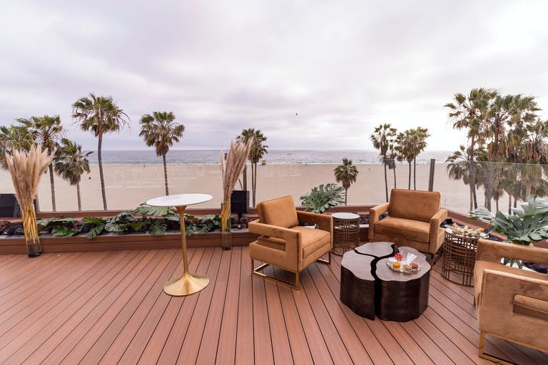 The Ocean Deck at The Penthouse on Venice Beach with pampas grass décor and tan lounge seating | PartySlate