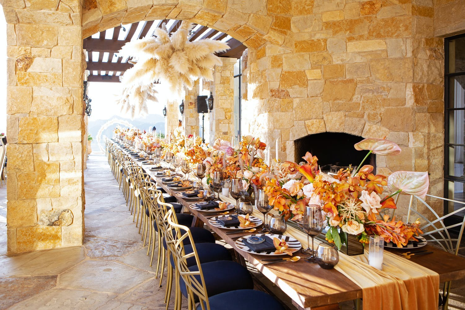 Fall wedding centerpieces of suspended pampas grass and orange flowers   PartySlate