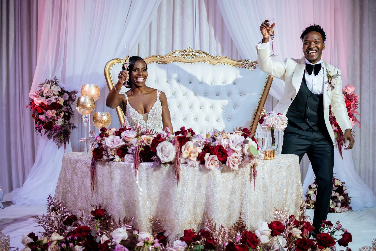 Bride and groom toast at sweetheart table with pink and red flowers on table and at foot of the table   PartySlate