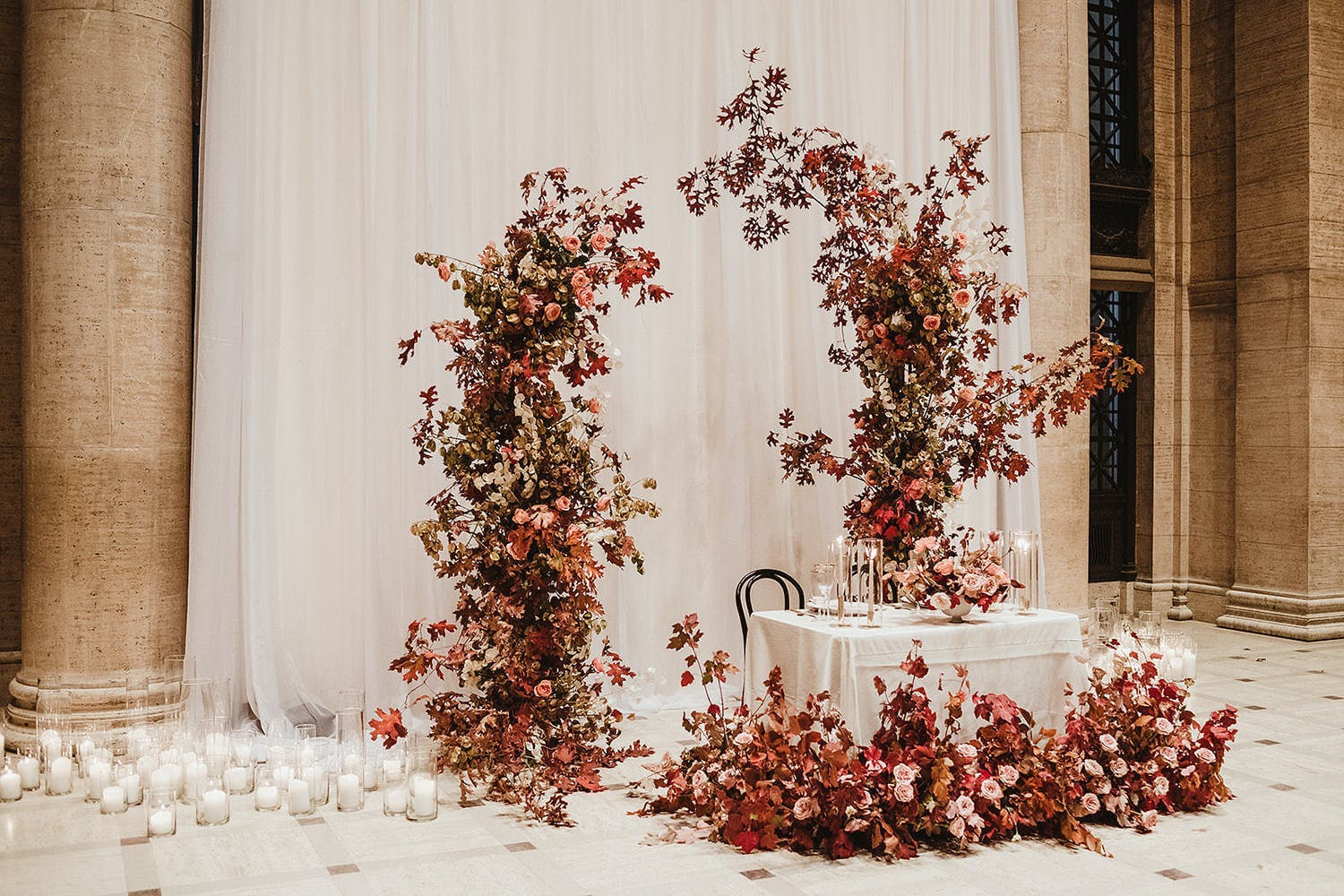 Sweetheart table with pink and champagne-hued floral centerpieces and asymmetrical backdrop   PartySlate