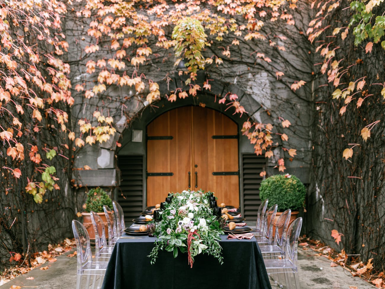 Fall tablescape with foliage table runner, black velvet linen, ghost chairs, and backdrop of ivy and fall-hued florals on stone wall   PartySlate