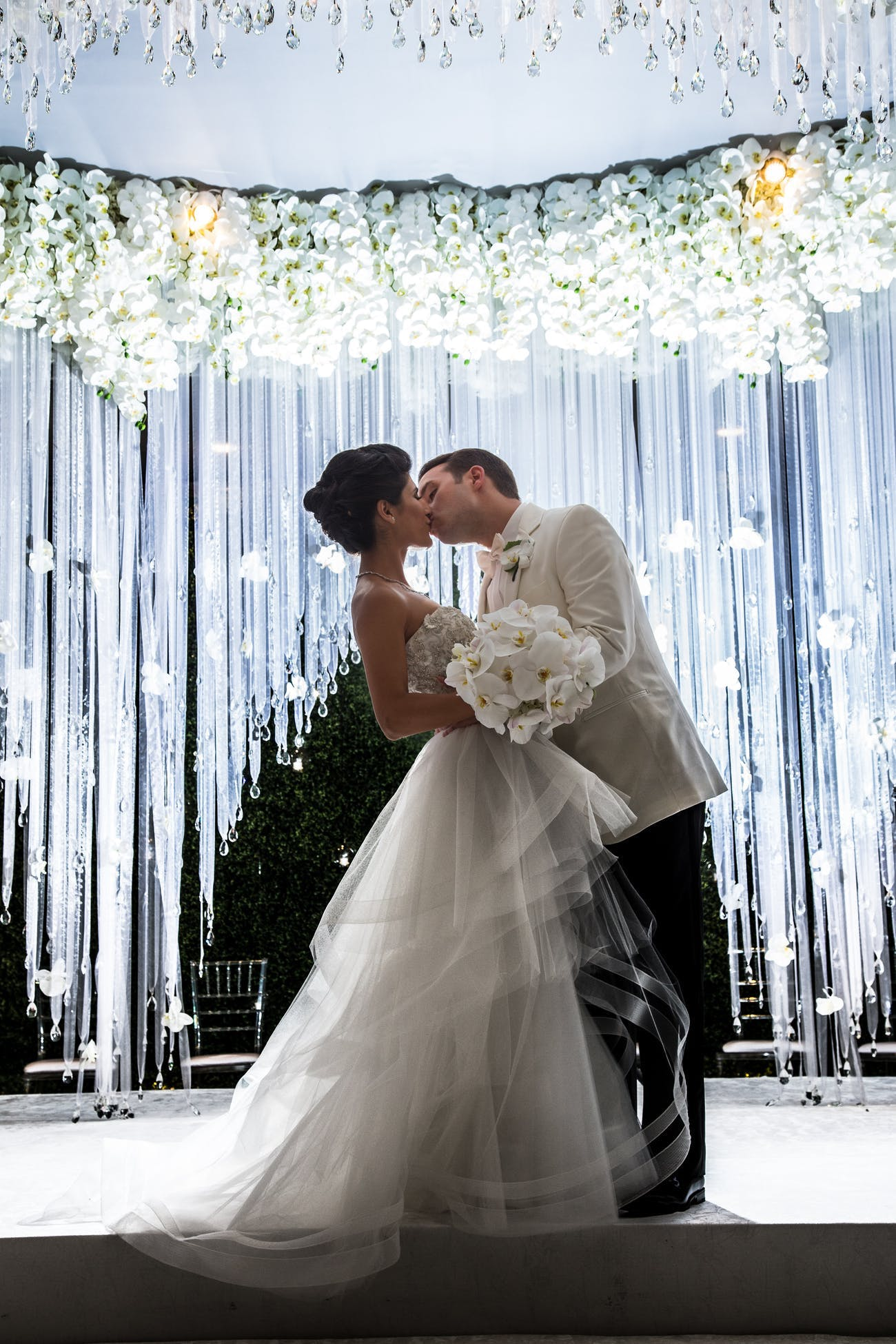 Bride and Groom Kiss in Front of Shimmering Tassel Backdrop Crowned with White Florals   PartySlate