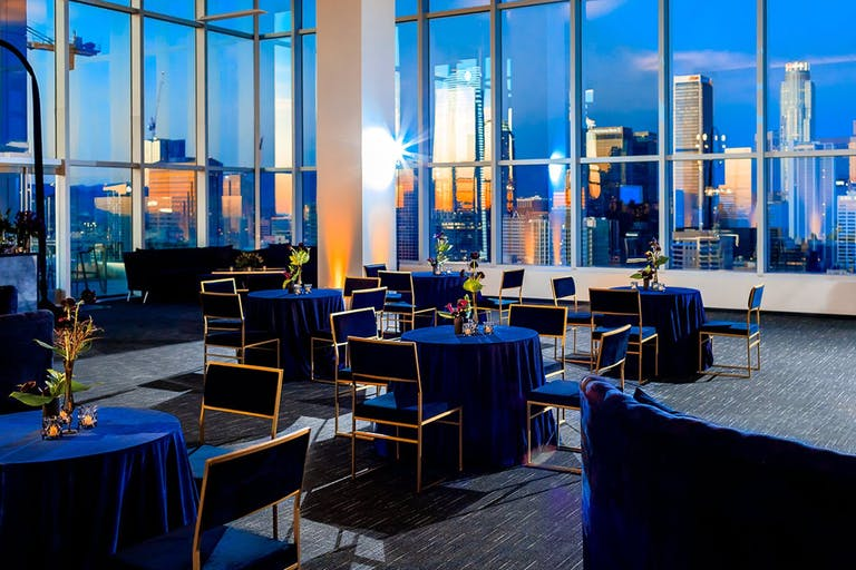 Party with blue lounge seating at Penthouse Suites at South Park Center with dramatic view of Los Angeles, CA | PartySlate
